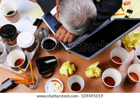 Closeup view of a very cluttered and stressed out businessman's desk. Overhead view of the mature man's head on laptop keyboard and scattered coffee cups and office supplies. Horizontal format. - stock photo