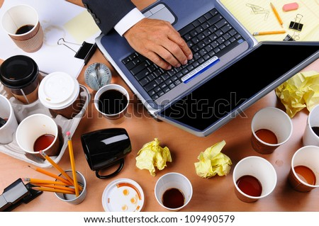 Closeup view of a very cluttered businessman's desk. Overhead view with man's hand on laptop keyboard and scattered coffee cups and office supplies. Horizontal format. - stock photo