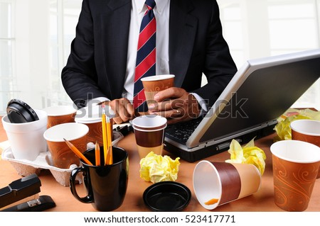 Closeup view of a very cluttered businessmans desk. Man is holding a coffee cup and crumpled papers litter his workspace. HIgh Key Office Background.