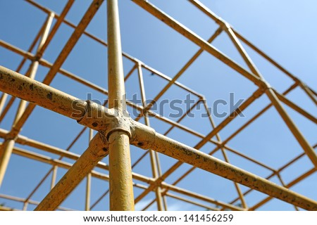 Closeup view of a yellow monkey bar metal frame in a children playground.  - stock photo