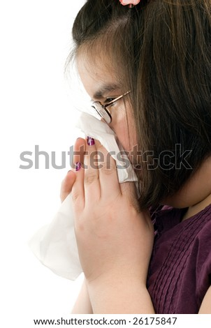 Closeup view of a young girl blowing her nose, shot on a profile view, isolated against a white background