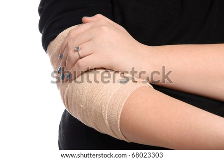 Closeup view of a young girl holding her  injured elbow, isolated on a white background. - stock photo