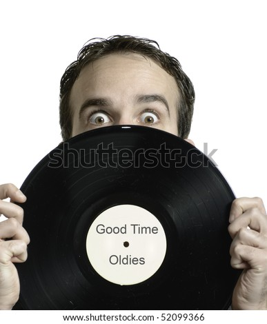 Closeup view of a young man holding an old lp record in front of his face, which says Good Time Oldies. *Text in image is done by photographer - stock photo