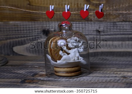 Closeup view of beautiful cupid angel decorative figurine near red paper greeting valentine clothes-peg in shape of heart with round pastry under glass flask on wooden background, horizontal picture - stock photo