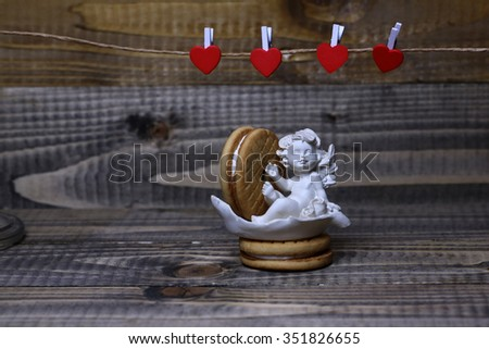Closeup view of beautiful cupid angel decorative figurine near red paper greeting valentine clothes-peg in shape of heart with round pastry on wooden background, horizontal picture - stock photo