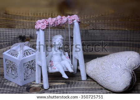 Closeup view of beautiful cupid angel decorative figurine near white paper valentine box and small pillow in shape of heart sitting on swing with pink roses on wooden background, horizontal picture - stock photo