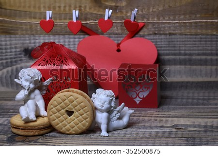 Closeup view of beautiful cupid angels decorative figurine near red paper greeting valentine box near clothes-peg in shape of heart with round pastry on wooden background, horizontal picture - stock photo