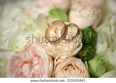 Closeup view of beautiful fresh soft wedding decorative bouquet of pink rose white peony and green flowers with two golden rings, horizontal picture - stock photo