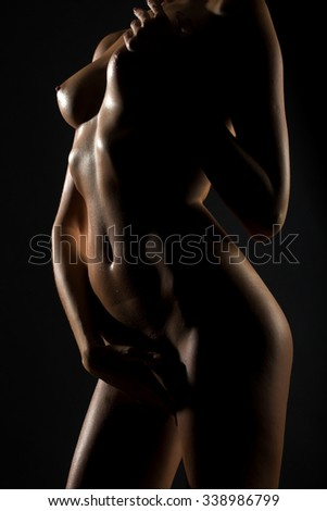 Closeup view of beautiful straight sexual naked female wet body chest belly torso and nipples of one young woman in studio on black background, vertical picture - stock photo