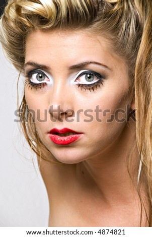closeup view of blond woman's face with 1950 style hair and makeup - stock photo