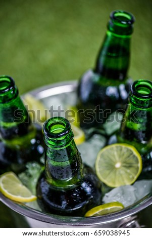 Closeup view of bucket full of ice cubes with opened beer bottles and lemon slices on green grass