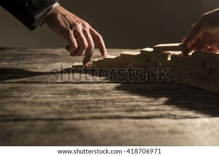Closeup view of businessman arranging wooden pegs in to a staircase like structure for his colleague to walk his fingers up the steps. Conceptual of business cooperation, vision and success. - stock photo