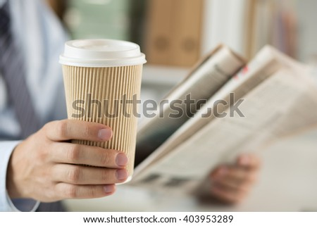 Closeup view of businessman hand holding cardboard coffee cup and reading morning newspaper. Financial or sports news, business analytics, coffeebreak or relaxing concept - stock photo