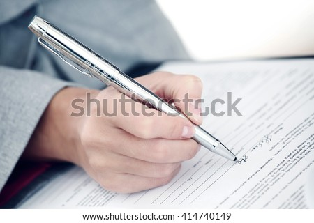 Closeup view of businesswoman hand signing a document - stock photo