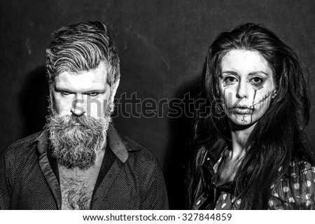 Closeup view of couple of painted halloween holy chracters woman and man with long lush beard looking forward on studio wall background black and white, horizontal picture - stock photo