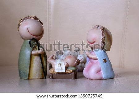 Closeup view of decorative celbrating Christmas and Jesus birth figurines of holy vergin Mary Josepd newborn child with few white sheeps standing on light leather background, horizontal picture - stock photo