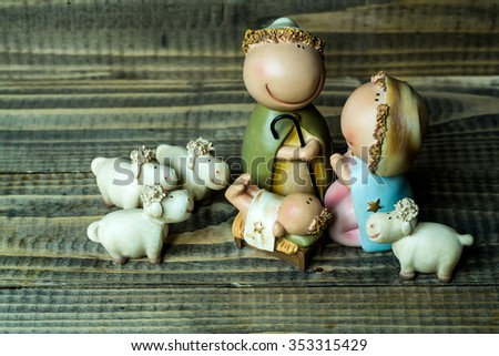 Closeup view of decorative celbrating Christmas and Jesus birth figurines of holy vergin Mary Josepd newborn child with few white sheeps standing on wooden background, horizontal picture - stock photo