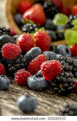Closeup view of delicious juicy ripe raspberries, strawberries, blackberries and blueberries scattering from a wooden bowl. - stock photo