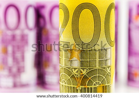 closeup view of 200 euro rolled banknote with the background made of another 500 euro banknotes blurred and rolled up - stock photo