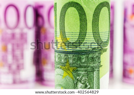 closeup view of 100 euro rolled banknote with the background made of 500 euro banknotes blurred and rolled up - stock photo