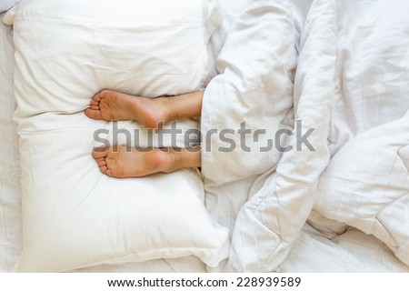 Closeup view of feet lying on soft white pillow at bed - stock photo