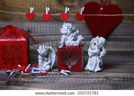 Closeup view of few beautiful cupid angels decorative figurine near red paper greeting valentine box and card on hanging ribbon on clothes-peg with no people on wooden background, horizontal picture - stock photo