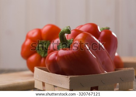 Closeup view of few fresh delicious sweet red ripe pepper in straw basket on wooden background, horizontal picture - stock photo