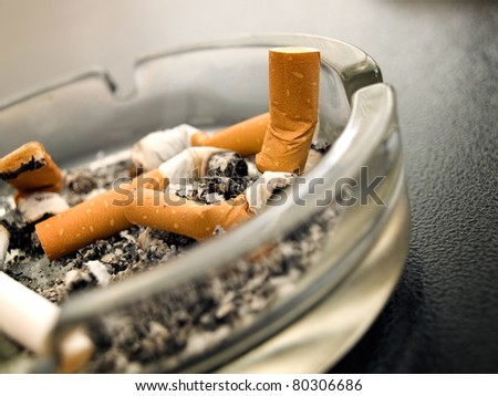 Closeup view of full ashtray on the table. - stock photo
