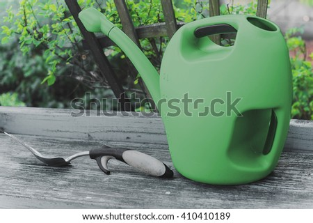 Closeup view of garden watering can and digging tool lying on weathered wooden bench, landscaping background. Focus on digging tool. - stock photo