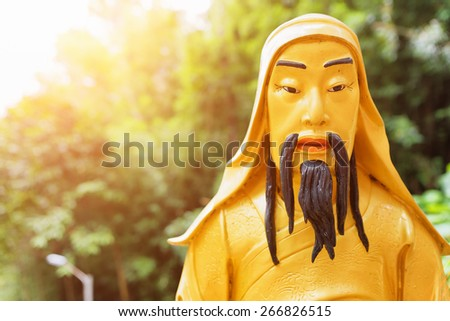 Closeup view of Golden Buddha statue in sunlight in the Ten Thousand Buddhas Monastery on nature background in Hong Kong. Hong Kong is popular tourist destination of Asia. - stock photo