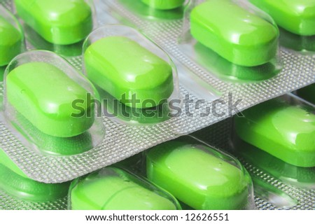 closeup view of green pills in plastic blister  from above