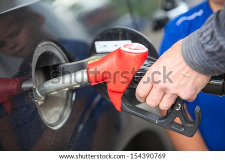 Closeup view of hand of driver inserting pumping nozzle with gasoline at the gas station - stock photo