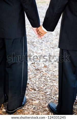 Closeup view of interracial gay couple getting married in tuxedos and holding hands.  Wedding band is visible. - stock photo