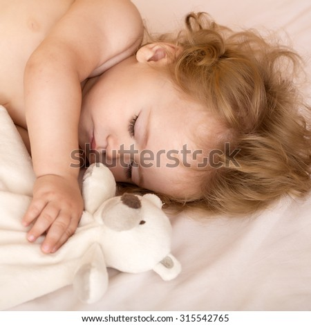 Closeup view of lovely little sleeping boy child with blonde curly hair round cheeks and tiny fingers lying with closed eyes in bed with plush stuffed bear toy on white background, square picture - stock photo