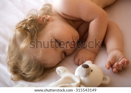 Closeup view of lovely small sleeping boy child with blonde curly hair round cheeks and tiny fingers lying with closed eyes in bed with plush stuffed bear toy on white background, horizontal picture - stock photo