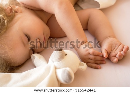 Closeup view of lovely small sleeping boy kid with blonde curly hair round cheeks and tiny fingers lying with closed eyes in bed with plush stuffed bear toy on white background, horizontal picture - stock photo