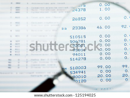 Closeup view of magnifying glass looking at financial report - stock photo