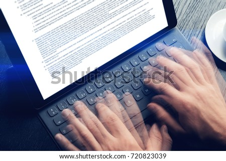 Closeup view of male hands quickly typing on electronic tablet keyboard-dock station. text information on device screen. Man working at office.Horizontal,cropp