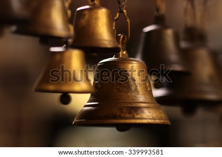 Closeup view of many beautiful old fashioned golden christmas bells hanging as new year toys, horizontal picture - stock photo