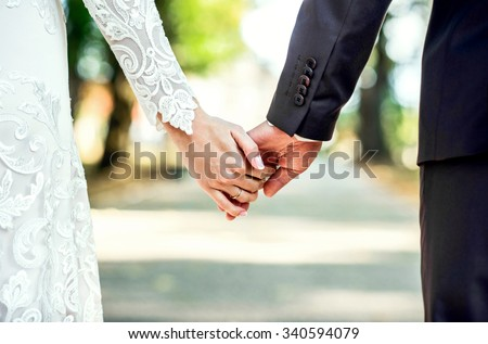 Closeup view of married couple holding hands  - stock photo