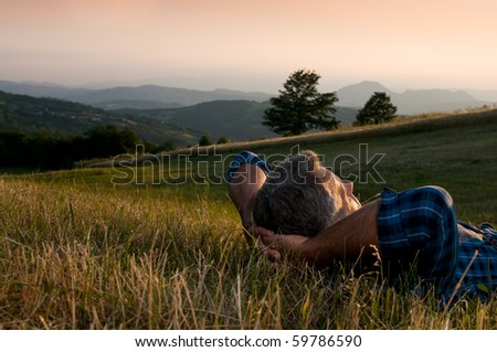 Closeup view of mature man taking a break and relax in a meadow in the wonderful warm light of the sunset - stock photo