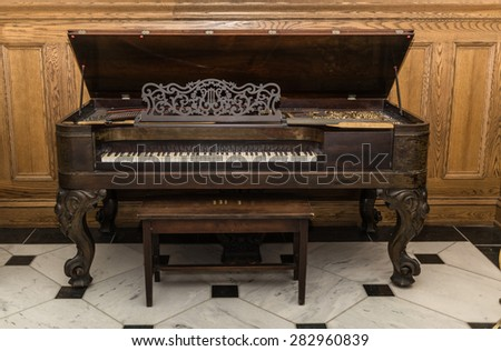 closeup view of old beautiful gorgeous vintage piano standing against wooden background - stock photo