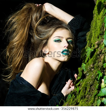 Closeup view of one attractive enigmatic glamour young woman with long hair and emeral bright makeup with bare shoulder near tree trunk with green moss in evening forest outdoor, square picture - stock photo