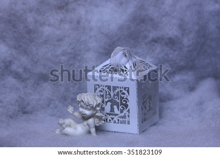 Closeup view of one beautiful cupid angel decorative figurine near paper greeting valentine box on white wadding decorating snow background, horizontal picture - stock photo
