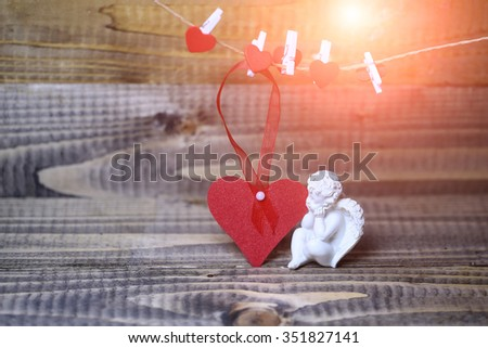 Closeup view of one beautiful cupid angel decorative figurine near red paper greeting valentine card on hanging ribbon on clothes-peg with no people on wooden background copy space, horizontal picture - stock photo