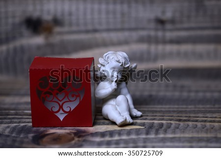 Closeup view of one beautiful cupid angel decorative figurine near red paper greeting valentine box in shape of heart with no people on wooden background, horizontal picture - stock photo