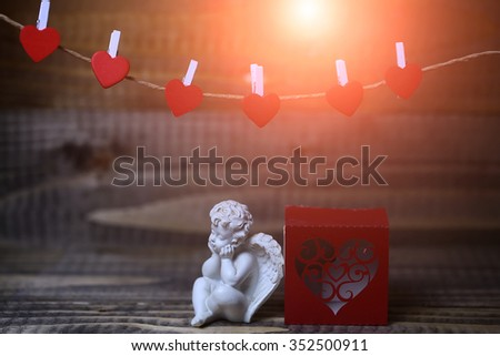 Closeup view of one beautiful cupid angel decorative figurine near red paper greeting valentine box near clothes-peg in shape of heart with no people on wooden background, horizontal picture - stock photo