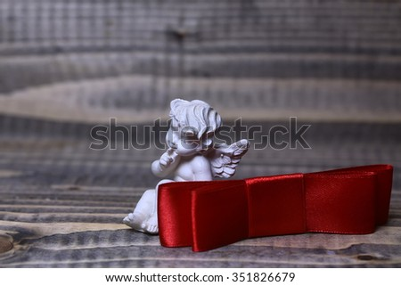 Closeup view of one beautiful cupid angel decorative figurine near red valentine silk ribbon bow with no people on wooden background copy space, horizontal picture - stock photo