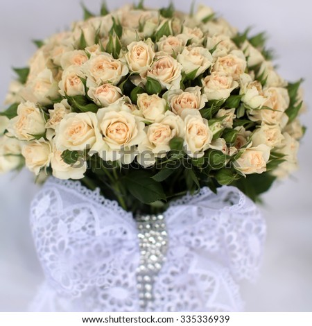Closeup view of one beautiful fresh bright white yellow big wedding bouquet of rose flowers with white lace bow, square picture