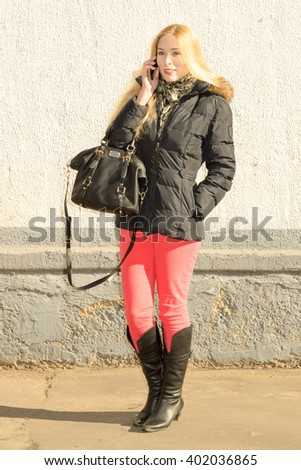 Closeup view of one beautiful young stylish woman with blonde lush long hair with a bag in black jacket and pink jeans standing outdoor speaking on mobile phone. white wall background, vertical - stock photo